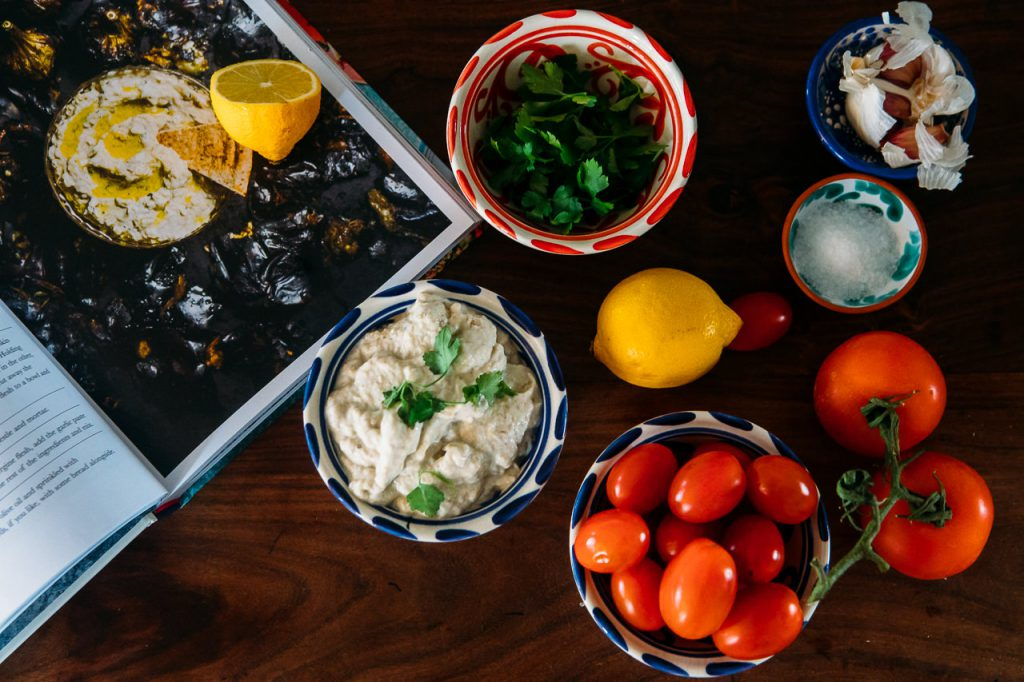 Aubergine dip, lemon and plum tomatoes in colourful dishes