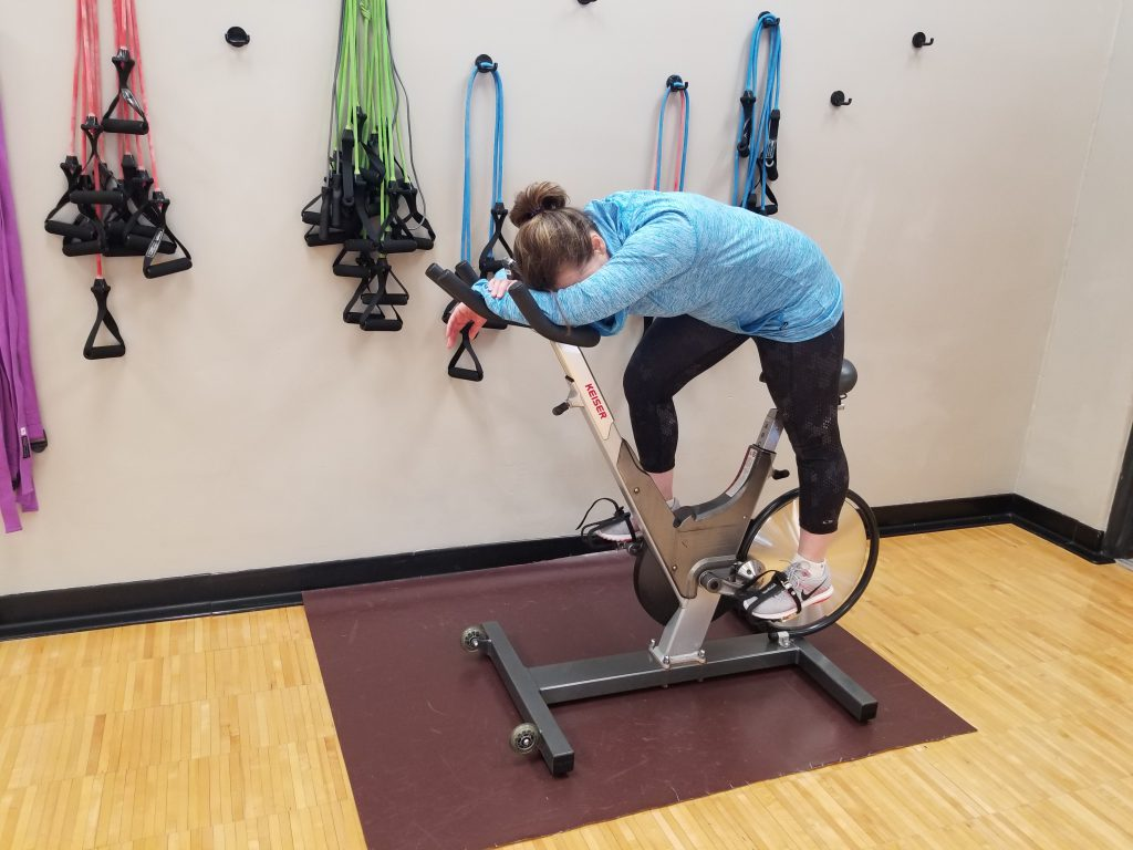 woman slumped over cycle machine at gym